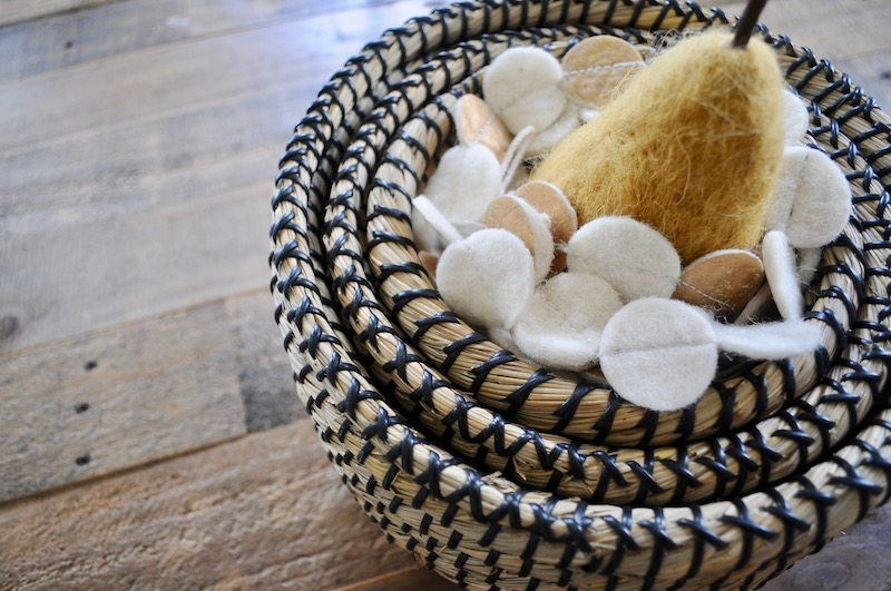 Fuzzy pear with gold and white garland in grass baskets
